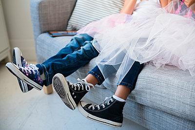Legs of girls wearing tutus on sofa - p555m1219514 by JGI/Jamie Grill