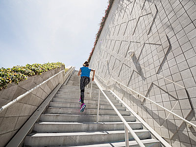 Caucasian woman running on staircase - p555m1303553 by Erik Isakson