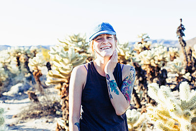 Caucasian woman smiling in desert field - p555m1410791 by Emily Suzanne McDonald
