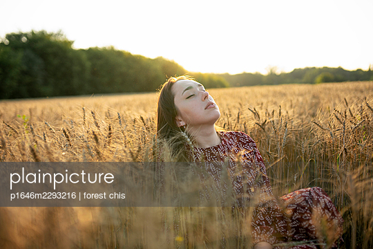 Young woman in a cornfield - p1646m2293216 by Slava Chistyakov