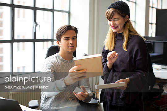 Smiling female entrepreneur discussing over product with male colleague at creative office - p426m2270542 by Maskot