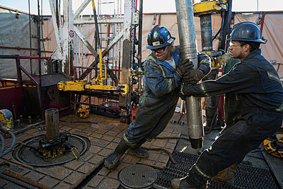 Male workers lifting drilling rig equipment gas plant - p1192m1128004f by Hero Images