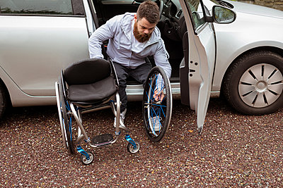 Disabled young man holding wheelchair while boarding in his car - p1315m1566289 by Wavebreak