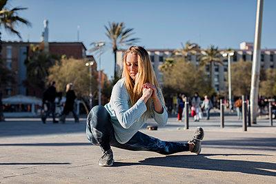 Spain, Barcelona, woman stretching leg on beach promenade - p300m2005494 von Mauro Grigollo