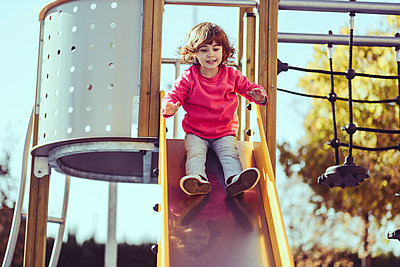 Portrait of little girl sitting on slide at playground - p300m2005558 von Javier Sánchez Mingorance