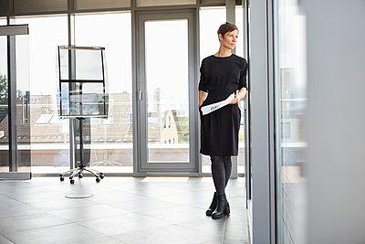 Businesswoman standing in office looking out of window - p300m2012970 von Rainer Berg