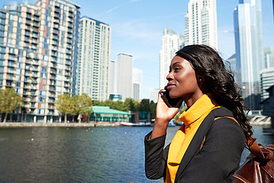 Female professional on phone call in front of river on sunny day - p300m2241586 by Pete Muller