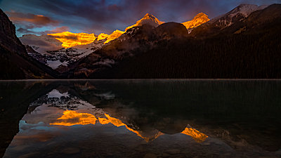 Golden sunlight illuminating the mountain peaks and reflecting in the tranquil water of Lake Louise, Banff National Park; Alberta, Canada - p442m1580506 by Aaron Von Hagen
