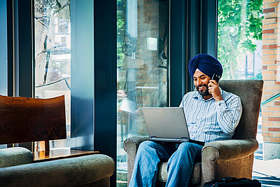 Man wearing turban using laptop and cell phone in armchair - p555m1304503 by Inti St Clair