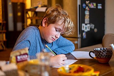 Boy doing his homework - p890m2045454 by Mielek
