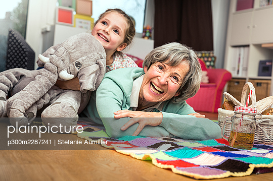 Girl leaning with toy on woman lying down in nursery - p300m2287241 by Stefanie Aumiller