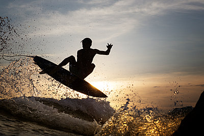 Young male surfer jumping over sea during sunset - p1166m1140256 by Cavan Images