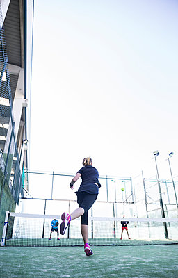 Side view of woman playing tennis with friend in court - p1166m1534524 by Cavan Social