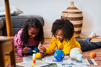 Sisters painting sphere while making solar system at home - p1166m2163325 by Cavan Images