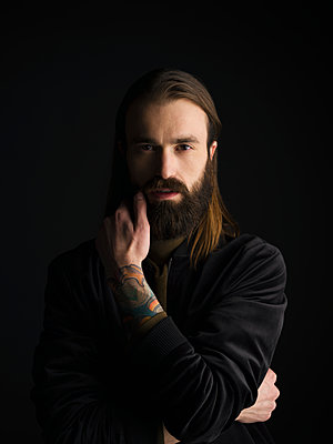 Portrait serious tattooed brunette man with beard against black background - p1192m1403628 by Hero Images