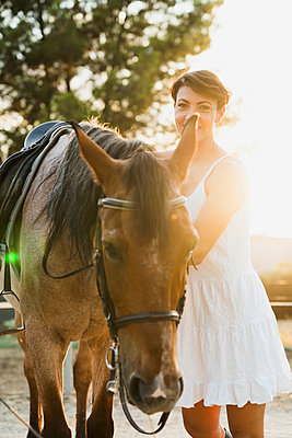 Portrait of smiling woman standing besides riding horse at backlight - p300m2042143 by Kike Arnaiz