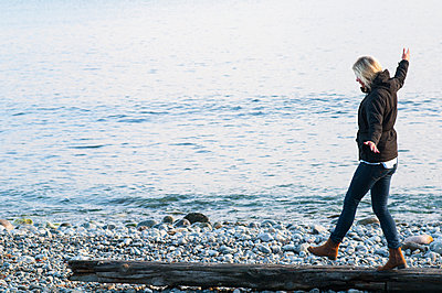 Sweden, Stockholm archipelago, Sodermanland, Toro, Young woman walking along log by sea - p352m1126892f by Christian Ferm