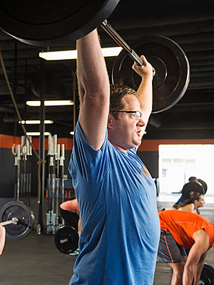 Man lifting weights in gym - p555m1419254 by Erik Isakson