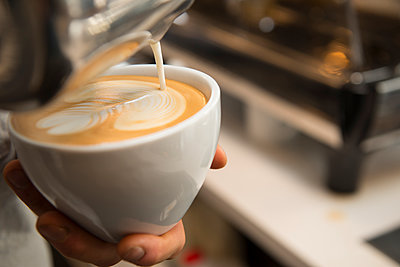 Cropped image of hands making pattern with cream on coffee - p1166m1532171 by Cavan Social