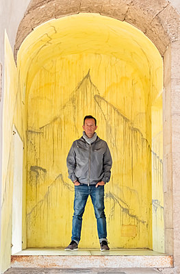 Adult man standing hands in pockets under an ancient arch - p1166m2072210 by Cavan Images