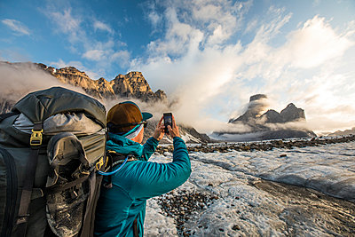 Backpacker uses smartphone to take a photo of Mount Asgard. - p1166m2189685 by Cavan Images