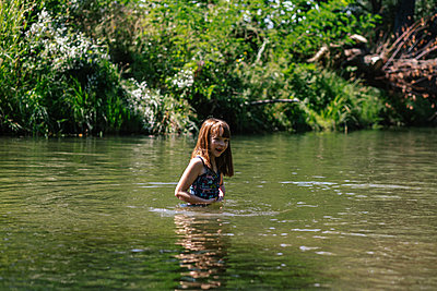 Happy young girl swimming in a deep creek on a summer day - p1166m2233048 by Cavan Images