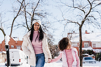 happy mother and daughter in the snow, madrid, Spain - p300m2251236 von Eva Blanco