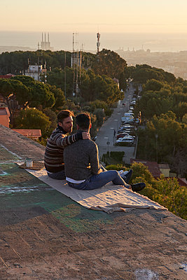Gay boyfriends talking while sitting on observation point during sunrise, Bunkers del Carmel, Barcelona, Spain - p300m2257337 by Veam
