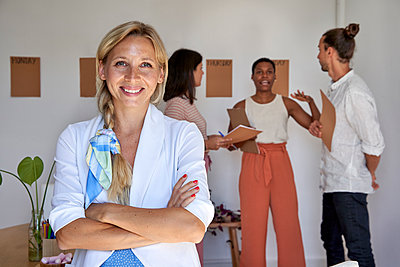 Blond businesswoman with arms crossed standing in office - p300m2294226 by Veam