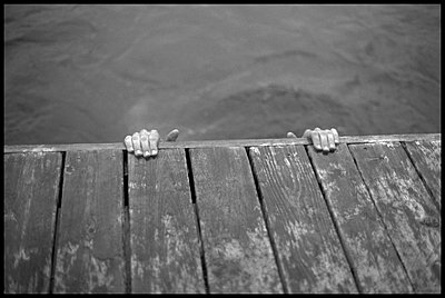 Hands gripping edge of dock - p3720273 by James Godman