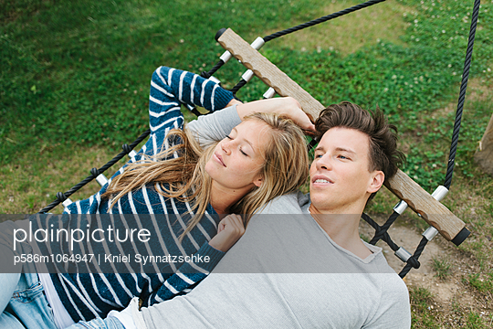 Young couple relaxing in hammock - p586m1064947 by Kniel Synnatzschke