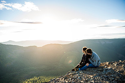 Couple sitting on mountain cliff and looking at view - p1166m1142701 by Cavan Images