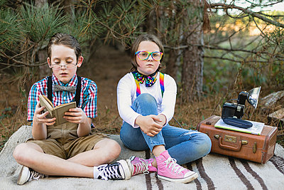 Siblings in old-fashioned costume sitting on blanket with antique camera at forest - p1166m1186064 by Cavan Images