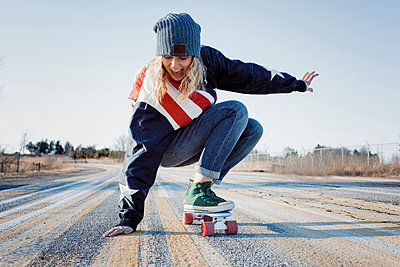 Full length of playful woman skateboarding on road during winter - p1166m1567607 by Cavan Images