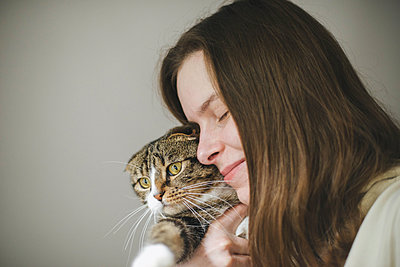 Young woman holding beautiful cat on white background - p1166m2255304 by Cavan Images