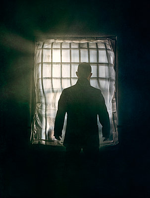 Imprisoned man looking out of window - p1280m2263561 by Dave Wall