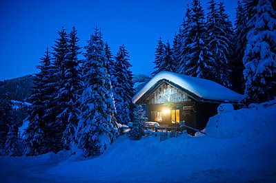 Austria, Altenmarkt-Zauchensee, sledges, snowman and Christmas tree at illuminated wooden house in snow at night - p300m2042030 by Hans Huber