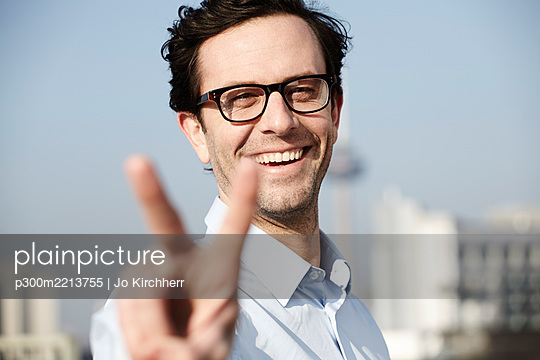 Portrait of smiling man showing victory sign - p300m2213755 by Jo Kirchherr