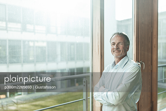 Smiling male entrepreneur with arms crossed standing at glass window in office - p300m2265693 by Gustafsson