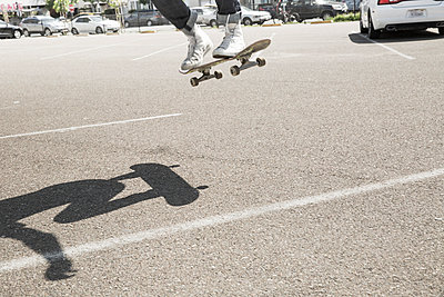Young man skateboarding in a car park. - p1100m1038912 by Mint Images