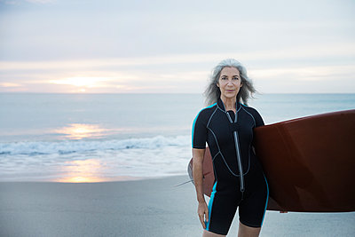 Portrait of confident female surfer carrying surfboard at Delray Beach - p1166m1141442 by Cavan Images