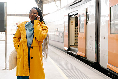 Portrait of smiling young woman on the phone standing on platform, Barcelona, Spain - p300m2166520 von COROIMAGE