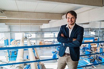 Young businessman with arms crossed smiling while standing at industry - p300m2250757 by Daniel Ingold