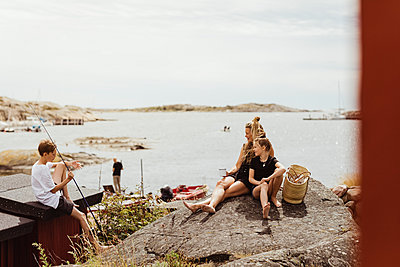 Mother and daughter sitting on rock while brother sitting by with fishing rod during sunny day - p426m2238361 by Maskot