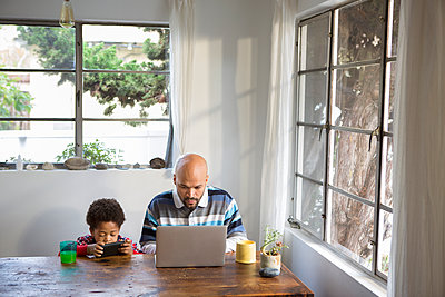 Mixed race father and son using technology at table - p555m1312277 by Sam Diephuis