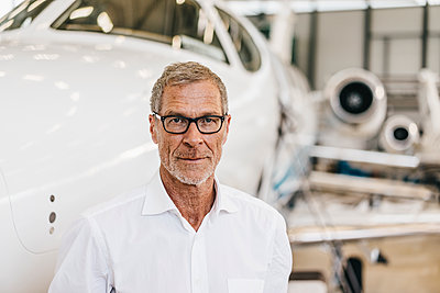 Mature businessman in front of his private jet - p586m1208523 by Kniel Synnatzschke