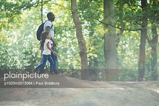 Father and daughter holding hands hiking in sunny summer woods - p1023m2213084 by Paul Bradbury