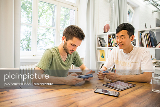Young men with tablet - p276m2110653 by plainpicture