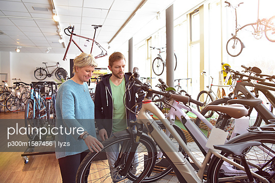 Salesman helping customer with e-bike - p300m1587456 von lyzs