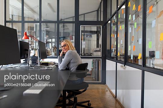 Mature businesswoman sitting at desk in office - p300m2156048 von Gustafsson